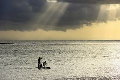 Cena do por do sol no fundo de vinda do temporal Um pai com tr?s crian?as est? remando em duas placas fotografia de stock