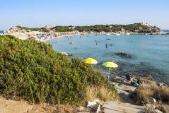 Cena do verão com os povos não identificados na praia branca e azul Imagens de Stock Royalty Free