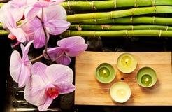 Cena dos termas com orquídeas, bambu e velas cor-de-rosa fotografia de stock royalty free