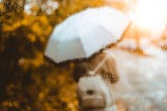 Cena dourada bonita do outono Aquarela como a menina loura borrada com trouxa e suportes de guarda-chuva brilhantes sob chuvoso fotos de stock