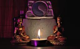 Cena: Duas estátuas diminutas da Buda, altar diminuto e vela iluminada, Fotos de Stock Royalty Free