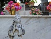 Cena em um cemitério: estátua de pedra de uma menina com mãos junto, rezar, olhando acima imagem de stock royalty free