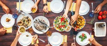 Cena grande de la familia Opinión vertical superior sobre la tabla con los platos foto de archivo