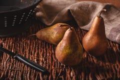 Cena imóvel da vida de três peras, de uma faca descascando, do escorredor e da toalha em um fundo tecido do galho imagens de stock royalty free