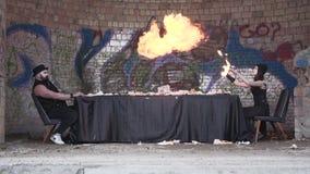 Cena incomum o homem e a jovem mulher farpados que sentam-se na tabela longa na frente da parede com grafittis A menina filme