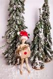 Cena invernal do Natal do feriado com o presente articulado de madeira da terra arrendada da posição da boneca que veste o chapéu imagem de stock