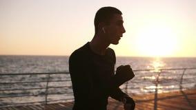Cena lindo de uma silhueta masculina do pugilista que luta com o oponente invisível na parte dianteira o mar com o sol da manhã q vídeos de arquivo