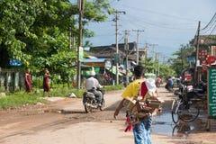 Cena local da rua no bago myanmar, homem que leva brinquedos de madeira imagem de stock