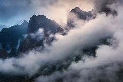 Cena majestosa com as montanhas nas nuvens na noite nublado Foto de Stock