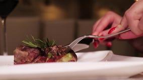 cena nel ristorante Le mani delle donne hanno tagliato la carne con un coltello e una forcella stock footage