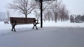 Cena nevando com o banco de parque no dia Paisagem nevado com arquitetura do parque público sob nuvens nublados filme