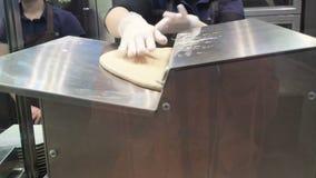 A cena: O cozinheiro passa a massa atrav?s do sheeter da massa, dando forma ? m?quina de rolamento da massa Produ??o de canela filme