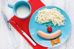 Cena o prima colazione per i bambini - spaghetti con la salsiccia e il vegeta Fotografia Stock