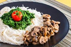 Cena - pastas con la espinaca y las setas Foto de archivo