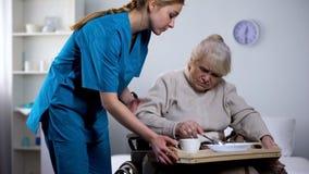 Cena poco apetitosa de la dieta de la porci?n de la enfermera a la vieja mujer perjudicada, tomando cuidado fotografía de archivo