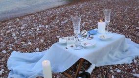 Cena por la luz de una vela en la playa Una tabla para una d romántica almacen de metraje de vídeo