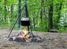 Cena que cocina sobre un fuego abierto imagen de archivo