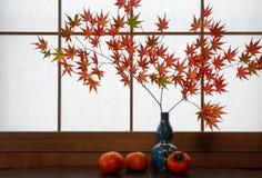 Cena rústica do outono das folhas de bordo japonesas vermelhas e de caquis maduros na frente de um fundo da janela do papel de ar Fotografia de Stock Royalty Free