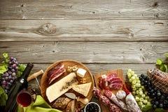 Cena romántica con el vino, el queso y las salchichas tradicionales Fotos de archivo libres de regalías