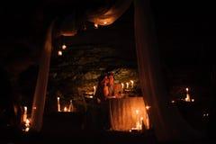 Cena romántica de un par joven por luz de una vela en las montañas foto de archivo