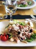 Cena romántica deliciosa: ensalada con los calamares, el pulpo, las aceitunas y los verdes imágenes de archivo libres de regalías