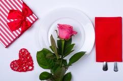 Cena romántica: la placa, cubiertos y subió en un fondo blanco Fotografía de archivo