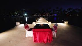 Cena romántica para las vacaciones de la luna de miel en la isla tropical Playa de Paradise en la noche con las luces que brillan