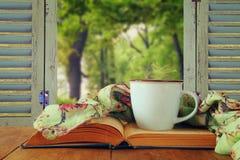 Cena romântica da xícara de café ao lado do livro velho na frente do cou Foto de Stock Royalty Free