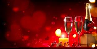 Cena romantica di giorno del ` s del biglietto di S. Valentino Champagne, candele e contenitore di regalo sopra fondo rosso Immagini Stock