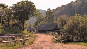 Cena rural Estrada à terra com as montanhas no fundo ver?o na vila Cerca de madeira na aldeia da montanha video estoque