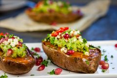 Cena sana - le patate dolci al forno sono servito con guacamole, feta ed il melograno immagine stock libera da diritti