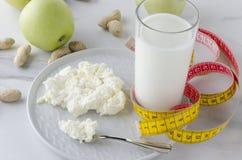 Cena sana, productos lechosos, manzanas, nueces, cinta métrica amarilla Concepto de peso de la pérdida, nutrición sana, comida, b fotos de archivo libres de regalías