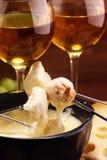 Cena svizzera gastronomica della fonduta su una sera di inverno con i formaggi assortiti su un bordo accanto ad un vaso heated de fotografia stock