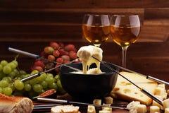 Cena svizzera gastronomica della fonduta su una sera di inverno con i formaggi assortiti su un bordo accanto ad un vaso heated de immagine stock