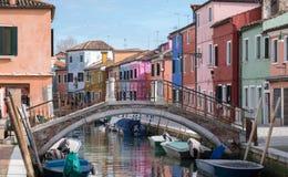 Cena típica da rua que mostra casas e a ponte brighly pintadas sobre o canal na ilha de Burano, Veneza foto de stock