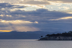 Cena tranquilo de raios do por do sol do shinig da luz através das nuvens imagens de stock royalty free