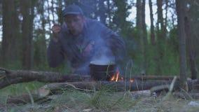 Cena turística de la ebullición y de los gustos de un fuego por la tarde del bosque metrajes