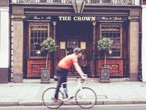 Cena urbana de um ciclista que anda na frente de um bar inglês Imagens de Stock