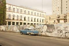 CENA VELHA da RUA de CUBA HAVANA COM GRAFITTIS na parede e NA PAREDE clássica do carro Imagens de Stock