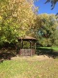 Cenador de madera en el parque soleado del oto?o imagen de archivo