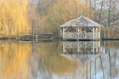 Cenador de madera en otoño por un lago con reflexiones Foto de archivo libre de regalías