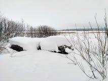 Cenas do inverno com as pedras cobertos de neve perto do lago gelado fotografia de stock