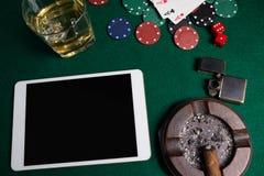 Cendrier, allumeur, comprimé numérique, matrice, puces de casino et cartes de jouer sur la table de tisonnier photos stock