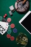 Cendrier, allumeur, comprimé numérique, matrice, puces de casino et cartes de jouer sur la table de tisonnier image stock