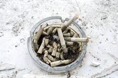 Cendrier complètement de bouts brûlés par cigarettes Image stock
