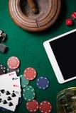 Cendrier, comprimé numérique, matrice, puces de casino et cartes de jouer sur la table de tisonnier images stock