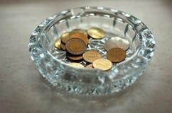 Cendrier en verre avec les pièces de monnaie Image libre de droits