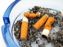 Cendrier en verre bleu avec la cigarette images libres de droits