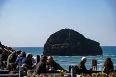 Cene che godono del pranzo ad un ristorante di vista di oceano al supporto di Trebarwith in Cornovaglia, Inghilterra Fotografia Stock