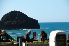 Cene che godono del pranzo ad un ristorante di vista di oceano al supporto di Trebarwith in Cornovaglia, Inghilterra Immagine Stock